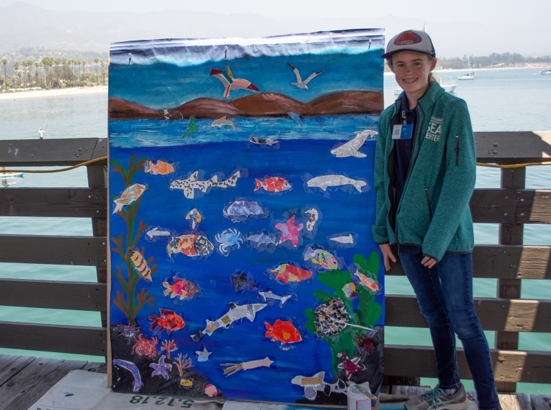 Lucy London as a young girl, standing at the Sea Center with the ocean in the background. She's next to a collage board as tall as her, covered with brightly colored paintings of marine life